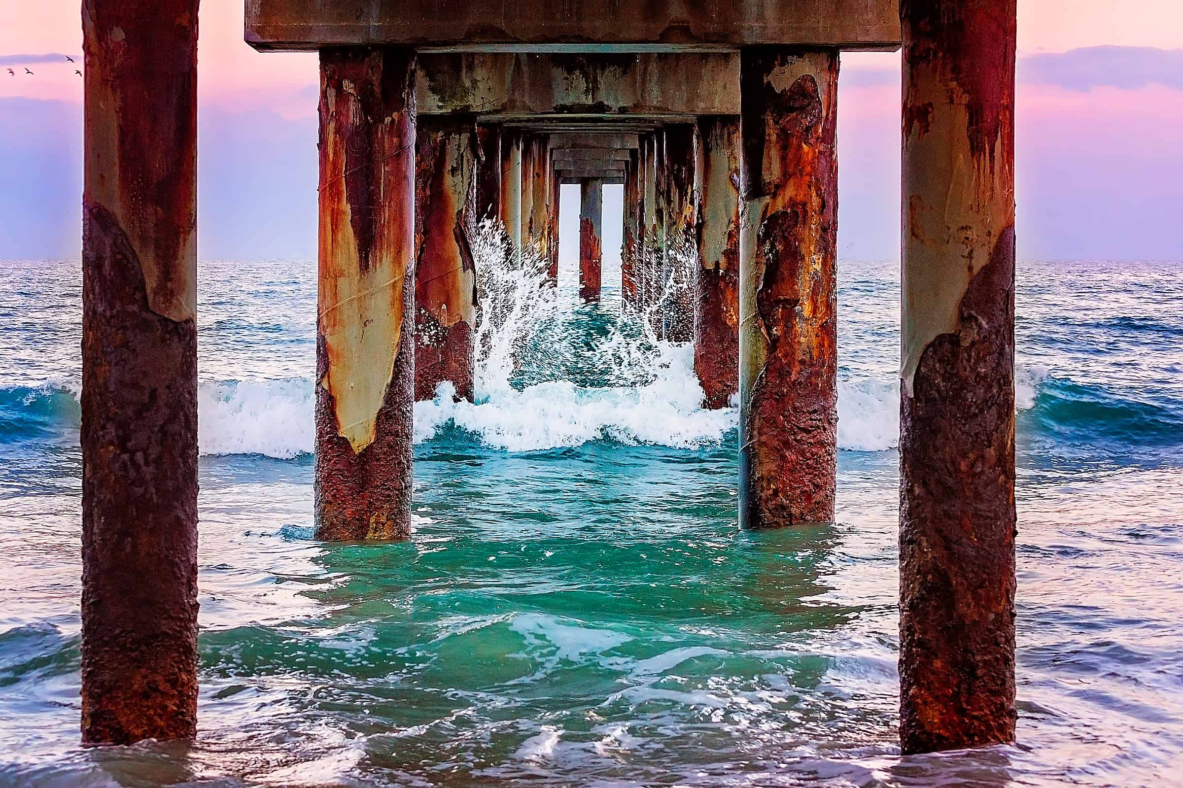 Waves crash beneath the St. Johns County Ocean Pier in St. Augustine, Florida