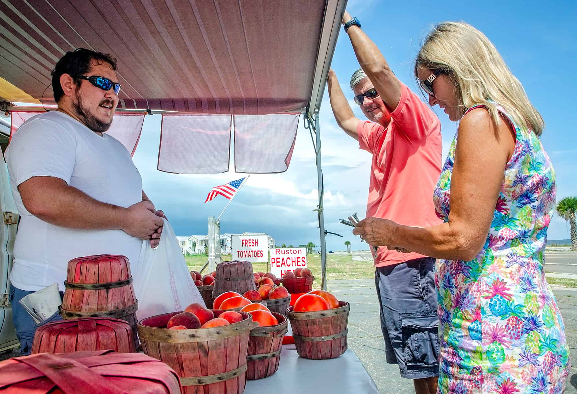 Fruit stand owner sells peaches to customers in Pass Christian Mississippi