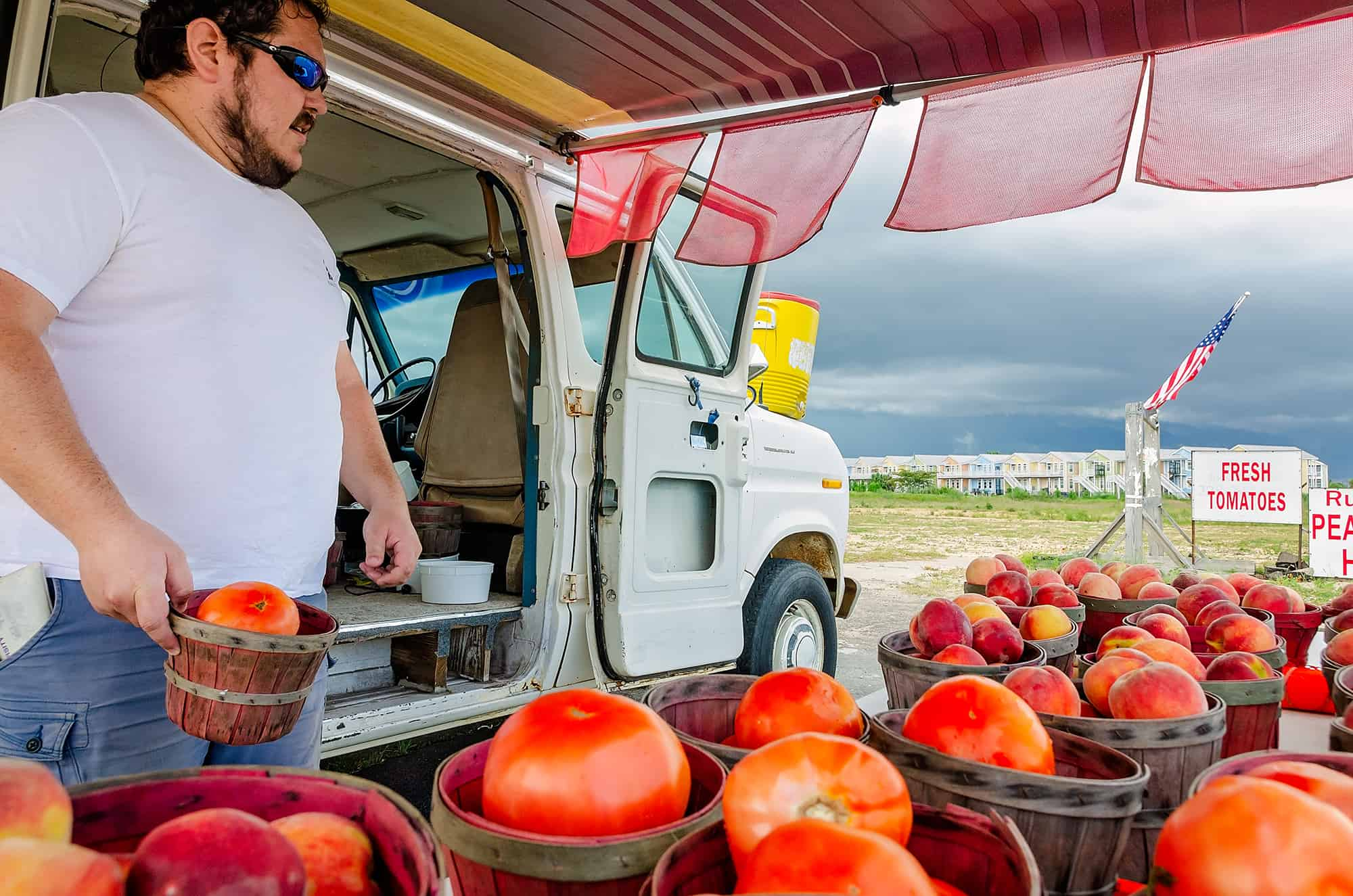 Fruit stand owner places Celebrity tomatoes on his table in Pass Christian Mississippi